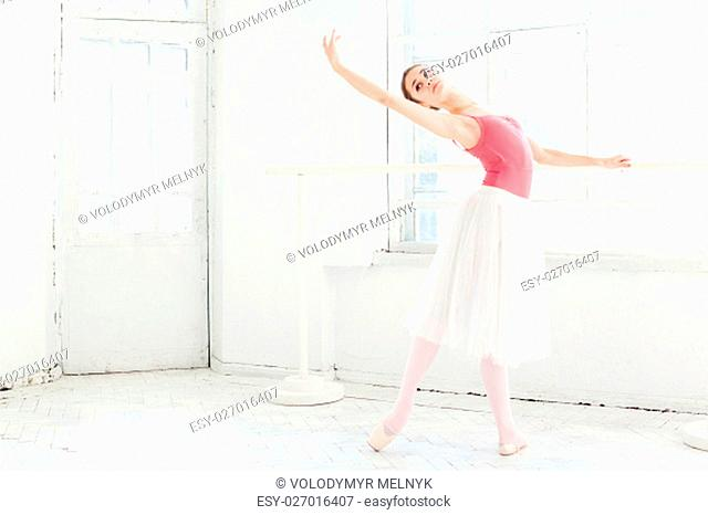 Ballerina posing in pointe shoes at the white wooden pavilion