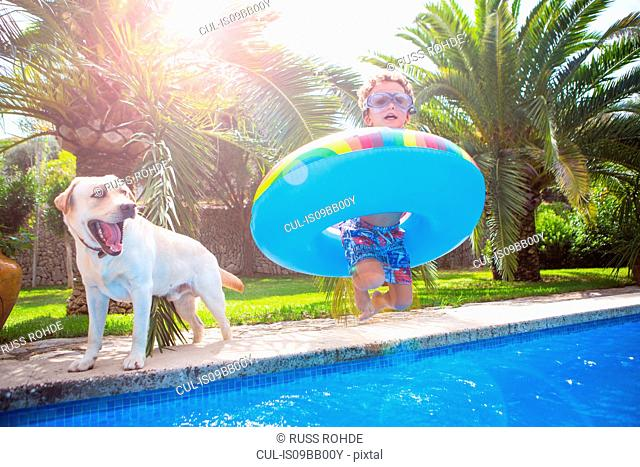 Boy with inflatable ring on poolside with golden retriever, portrait
