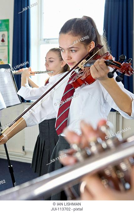 Focused high school student playing violin in music class