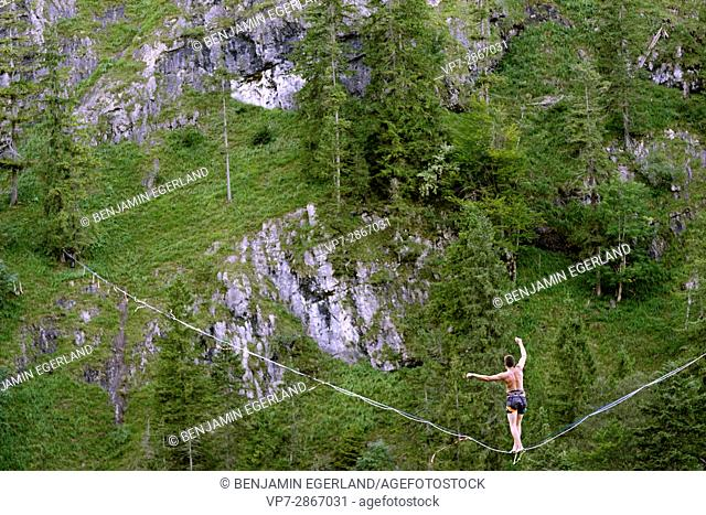 young outdoor sportsman balancing and walking on highline slackline over valley in nature, in south of Germany, Bavaria, near border to Austria