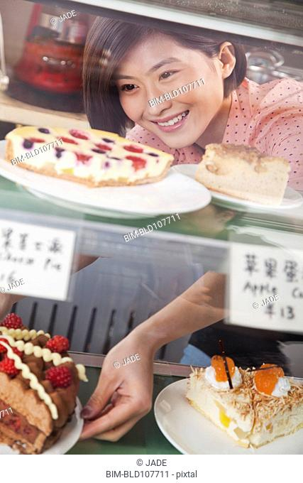 Chinese woman removing pie from display case