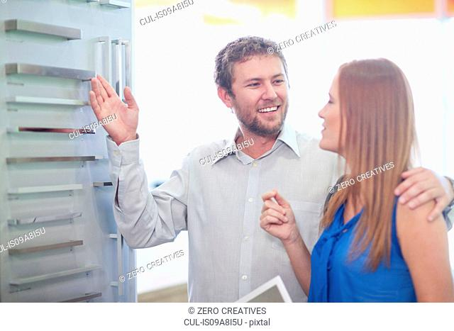 Young couple looking at handles in kitchen showroom