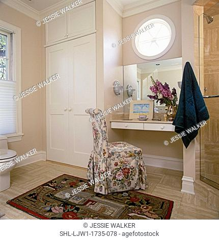 BATHROOMS: Vanity with a floral patterned slipper chair, closet, shower, round window, folk art hooked rug, neutral marble floors