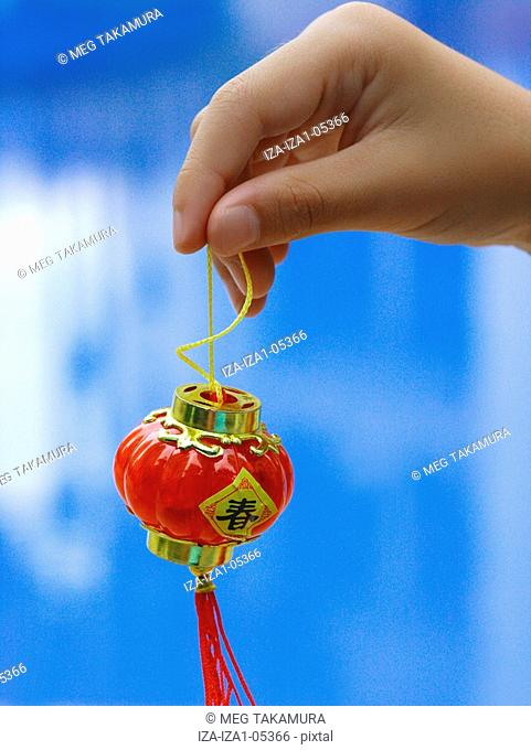 Close-up of a person's hand holding a tiny Chinese lantern