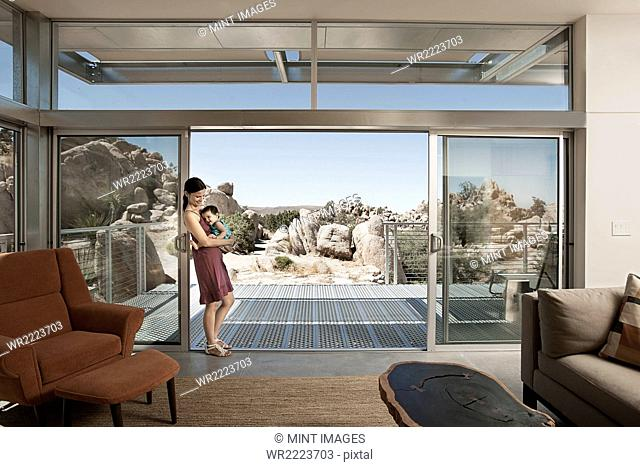 A woman and a young child in the living space of an eco house in the desert