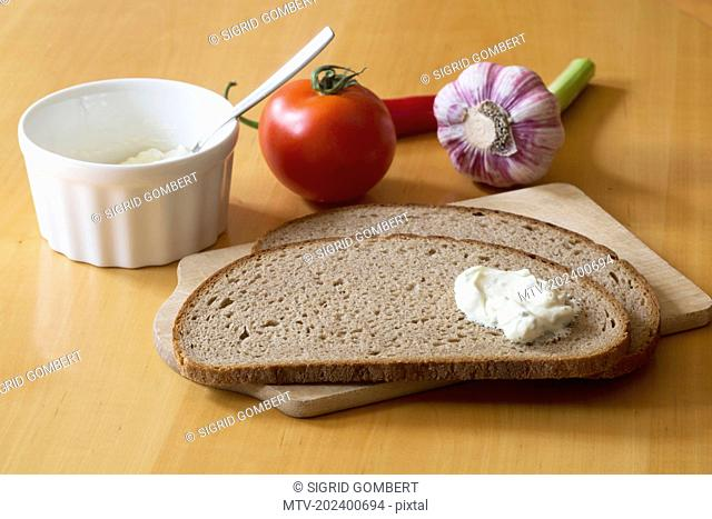 Two slices of bread, cheese, tomato onion on chopping board