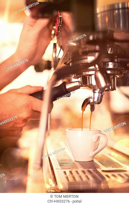 Close up barista using espresso machine in cafe