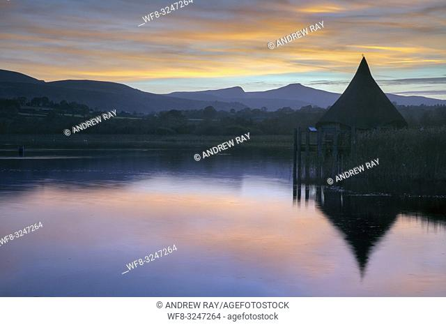 The Crannog at Llangorse Lake in the Brecon Beacons National Park captured at sunset with Pen y fan in the distance. The image was captured from a nearby jetty...