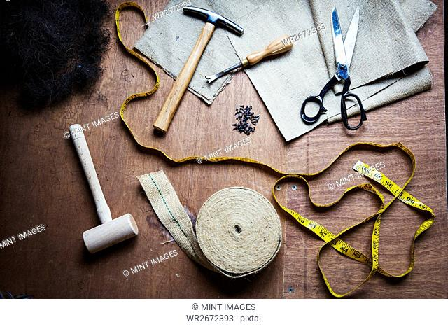 Upholstery workshop. Overhead view of hand tools, hammer, tape, tape measure and scissors
