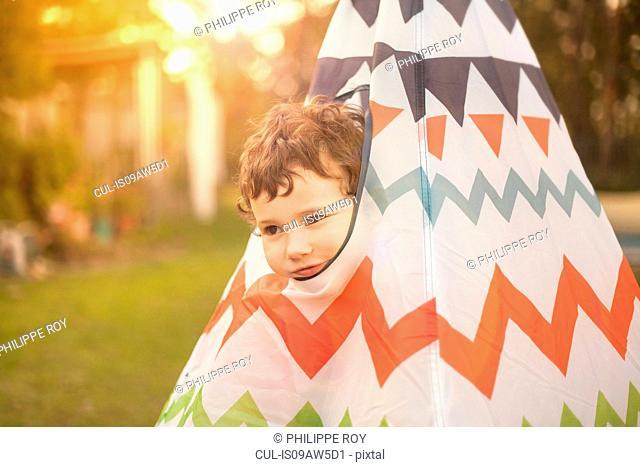 Boy in garden peeking out of teepee