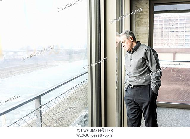Exhausted senior businessman leaning against window