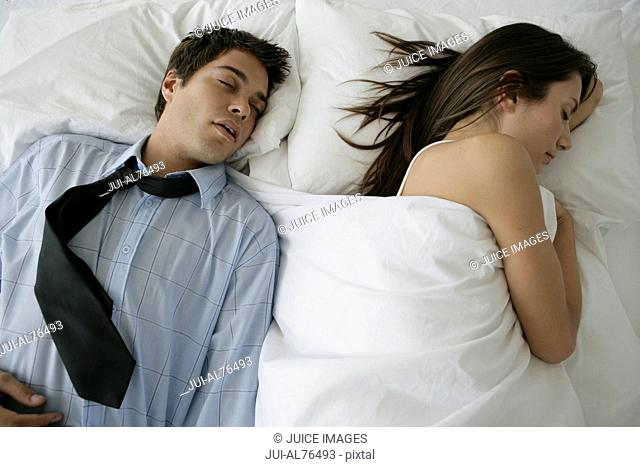 Portrait of a young man in work clothes asleep beside his girlfriend