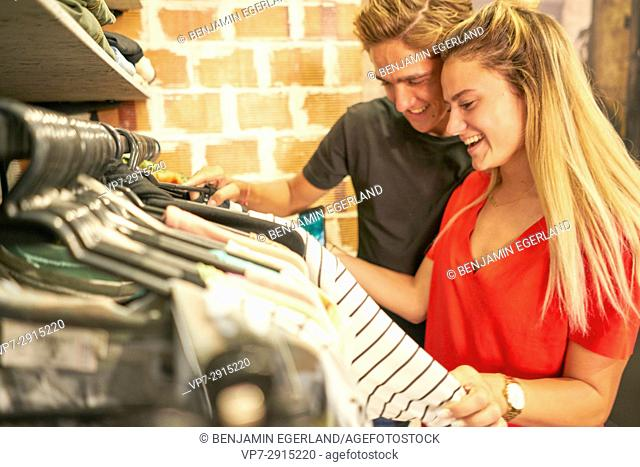 Happy young Dutch couple shopping together clothes in clothing fashion store