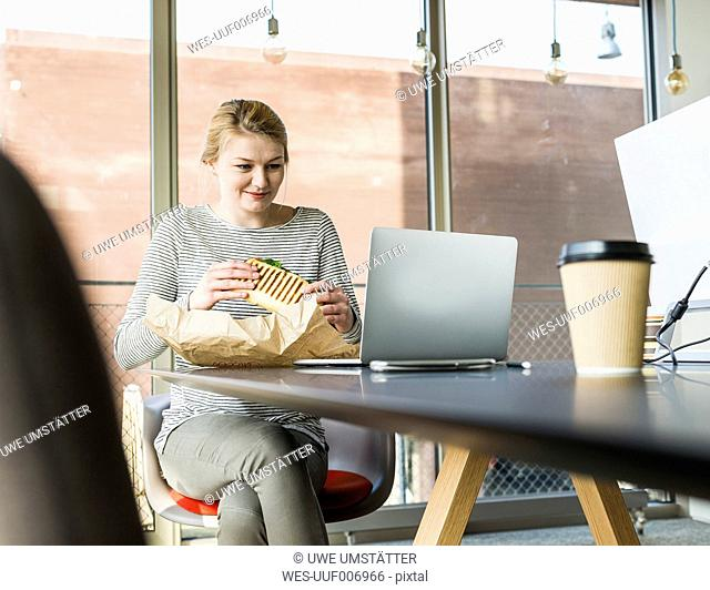 Young woman having lunch break in office