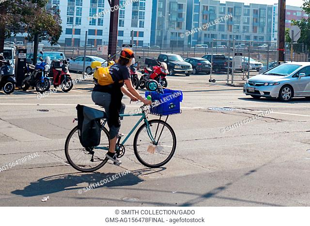 A woman wears a surgical face mask while biking in the South of Market (SoMA) neighborhood of San Francisco, California, October 13, 2017