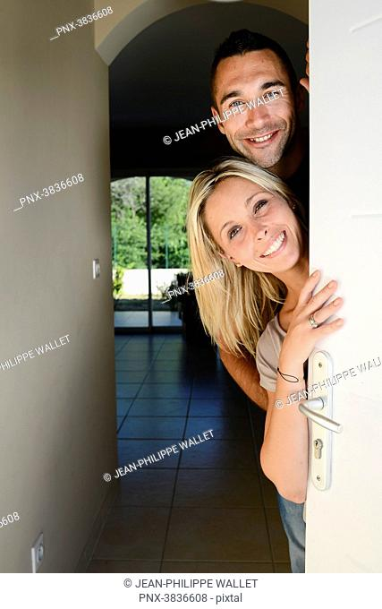 Happy young couple welcoming friends at the front door of new house