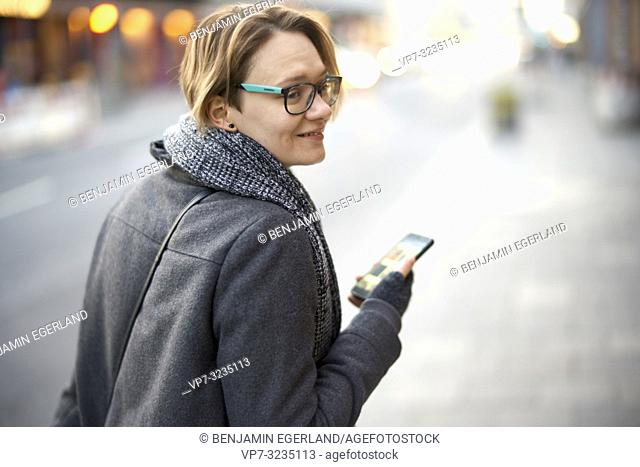 woman with smartphone in hand walking at street in city, Munich, Germany