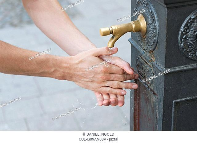 Hands of mid adult woman washing in water fountain, Sardinia, Italy