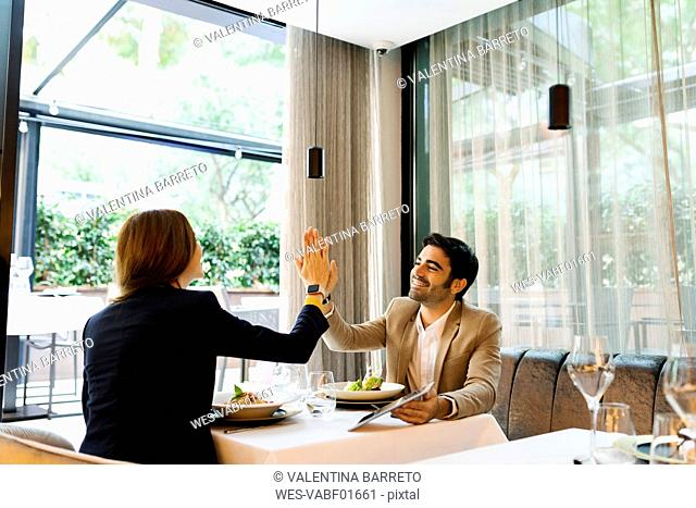 Happy man and woman with a tablet in a restaurant high fiving