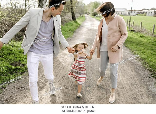 Little girl holding hands of parents while running