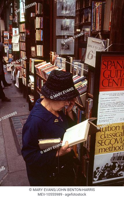 London Street Scene -- a woman peruses a book on the pavement outside a book shop