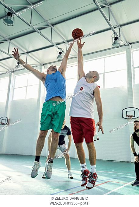 Men playing basketball, defence