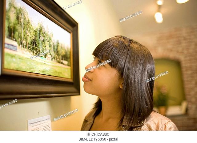 Mixed race woman admiring painting in gallery