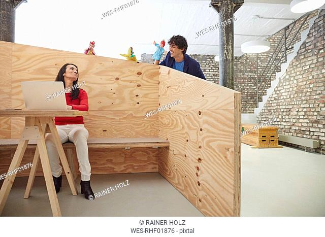 Businesswoman working on laptop with colleagues playing hand puppets behind wooden wall
