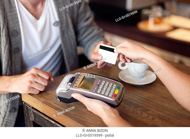 Close up of customer paying by credit card. Krakow, Poland