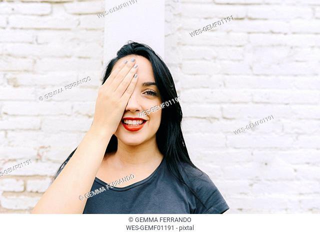 Portrait of young woman in front of brick wall covering one eye with hand