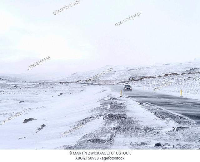 Mountain landscape in northern Iceland during winter.Road condition during winter in Iceland. Road covered with ice during snow storm