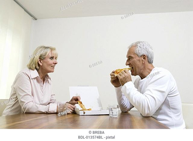 mature couple eating pizza together from takeout box