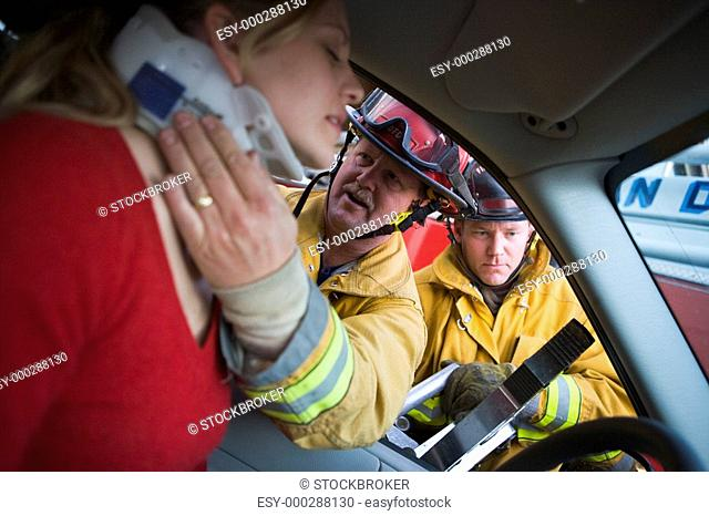 Fireman helping woman with neck brace while another fireman uses the jaws of life on a car door selective focus