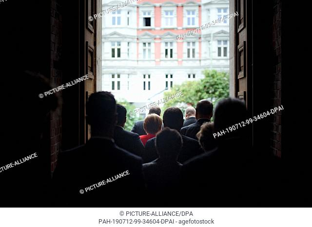 12 July 2019, Berlin: Federal Chancellor Angela Merkel (CDU, M) is leaving the venue accompanied by staff and hosts at the end of a ceremony marking the 50th...