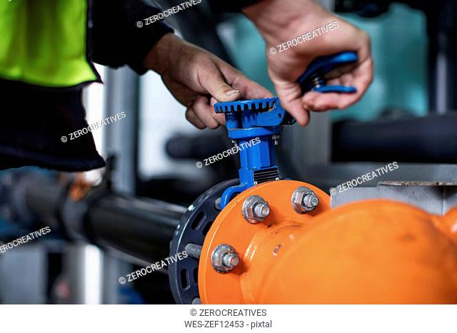 Hands turning valve in factory