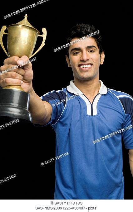Soccer player holding a trophy and smiling