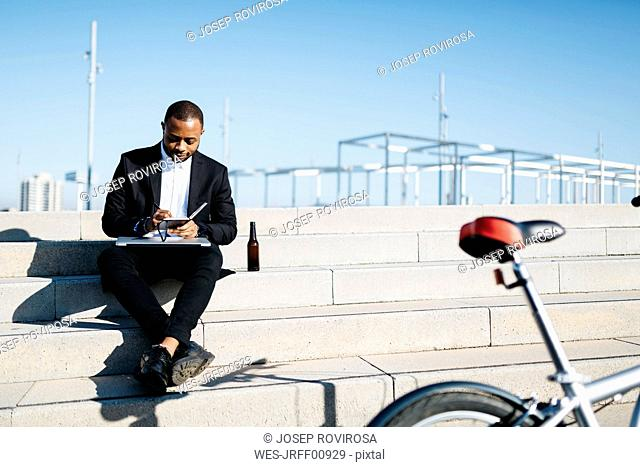 Businessman sitting on stairs with bottle of beer, notebook and laptop