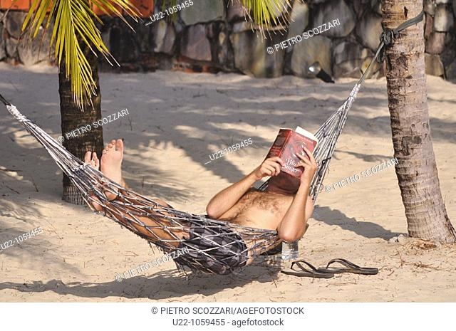 Sihanoukville (Cambodia): a tourist relaxing and reading a book on a hammock at Victory Beach