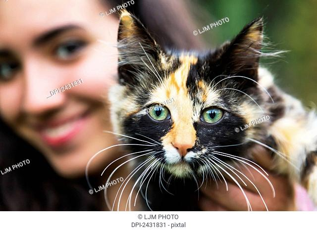 Young woman holding her cat; Sherwood Park, Alberta, Canada