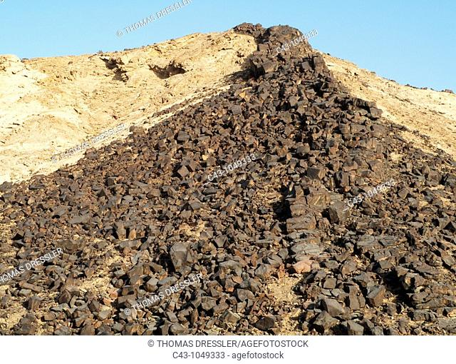 Namibia - A vein of basaltic rock emerged at the ridge of a rocky hill due to the erosion of the surrounding softer rock  East of Swakopmund