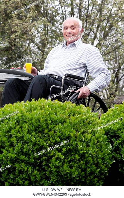 Portrait of a man sitting in a wheelchair and holding a glass of juice