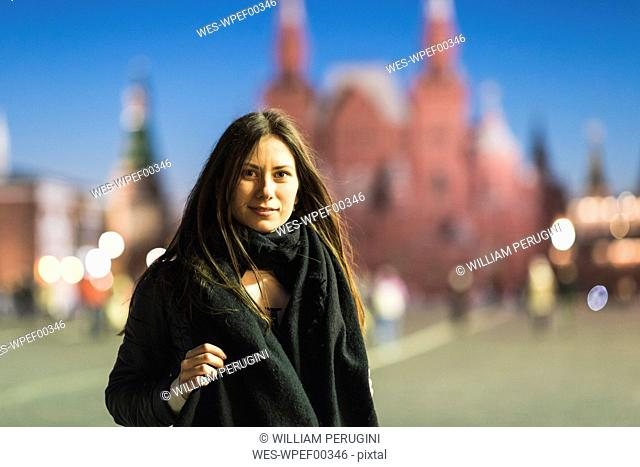 Russia, Moscow, young woman visiting Red Square at night
