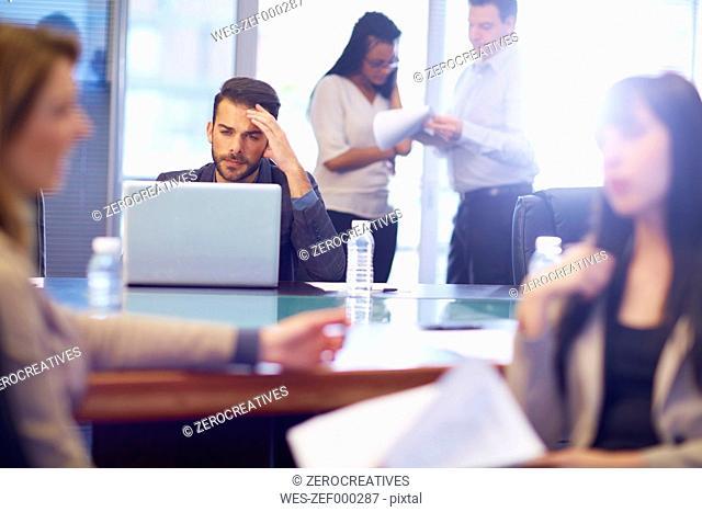 Businessman using laptop in boardroom