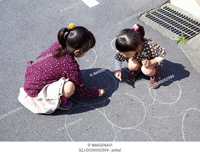 Girls drawing a picture with chalk
