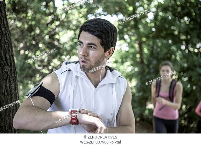 Man with watch running in forest listening to music