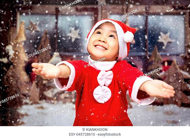 Asian Chinese little girl playing with snowflakes outdoor during christmas eve