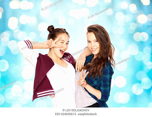 people, friends, teens and friendship concept - happy smiling pretty teenage girls showing peace hand sign over blue holidays lights background