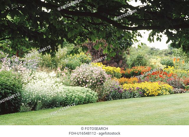 Orange and red perennials in large herbaceous border in country garden