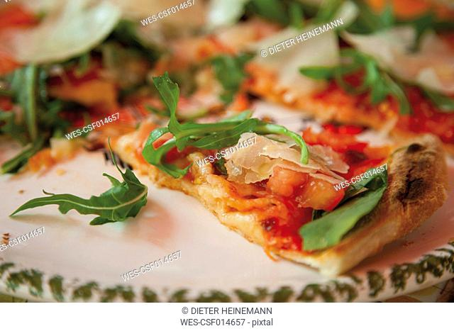Pizza garnished with rocket, tomatoes and parmesan, close up