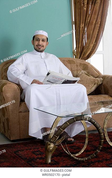 Arab man sitting in a sofa holding a newspaper